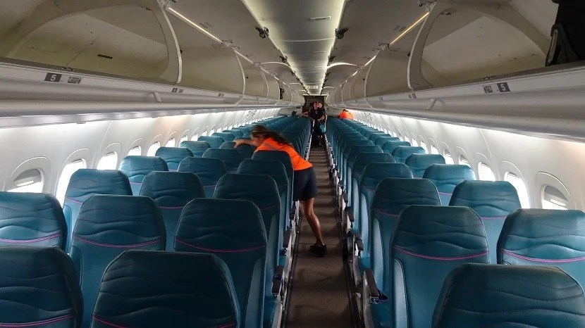 A crew member cleans the cabin of the B717, with seats in a 2-3 configuration.