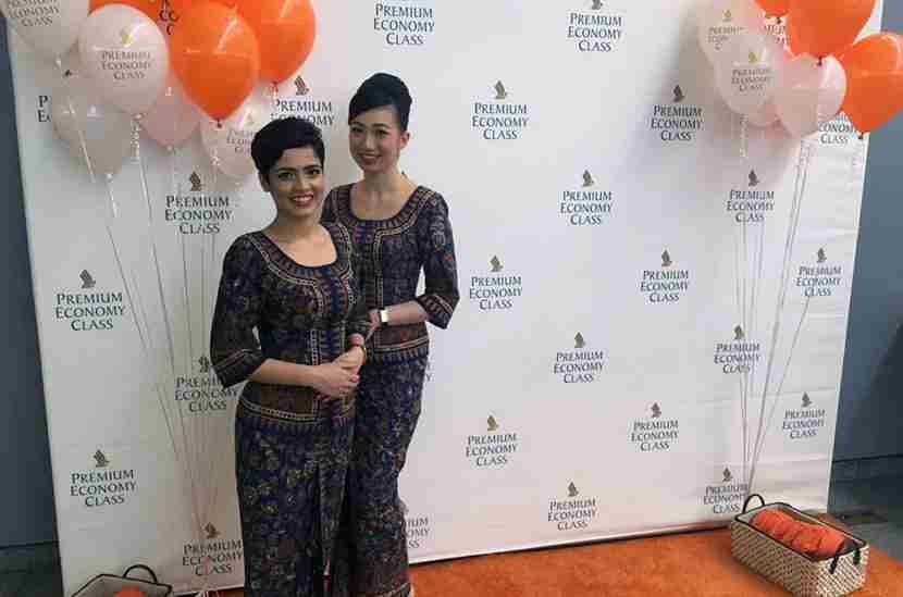 A couple of Singapore Girls were posing for pictures with passengers on the orange carpet.