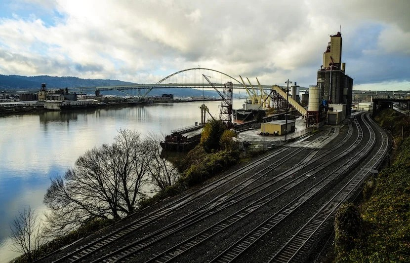 """Shipping remains an important industry to Portland, but with a questionable past. Image courtesy of <a href=""""http://www.shutterstock.com/pic-121934983/stock-photo-railroad-tracks-by-a-harbor-with-ship-loading-cargo.html?src=9YHTDeyNvrRHouY5Kg8gXw-1-23"""">Shutterstock</a>."""