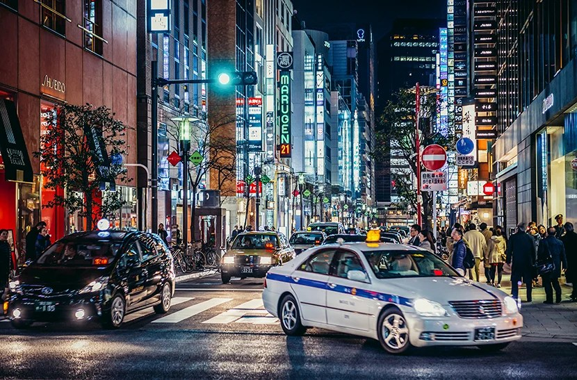 """Downtown Tokyo's Ginza buzzes with life at all hours. Image courtesy of <a href=""""http://www.shutterstock.com/pic-440976910/stock-photo-tokyo-japan-february-27-2015-view-on-one-of-the-streets-of-ginza-district-in-tokyo.html?src=DSzX352BrWn6JDRJXiS-Kw-1-28"""">Shutterstock</a>."""