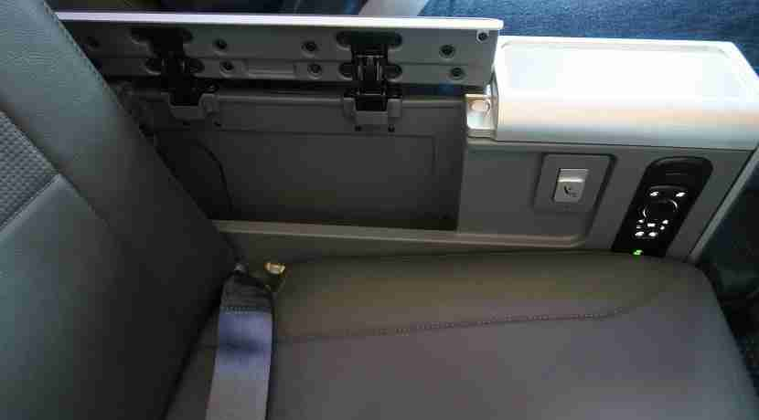 Each premium economy seat has a storage well under one of the armrests.