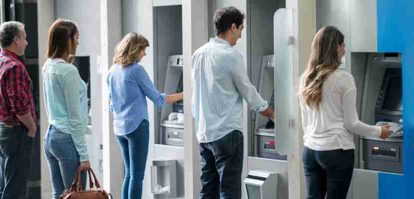 Taking out cash at an ATM. Image courtesy of Getty Images.