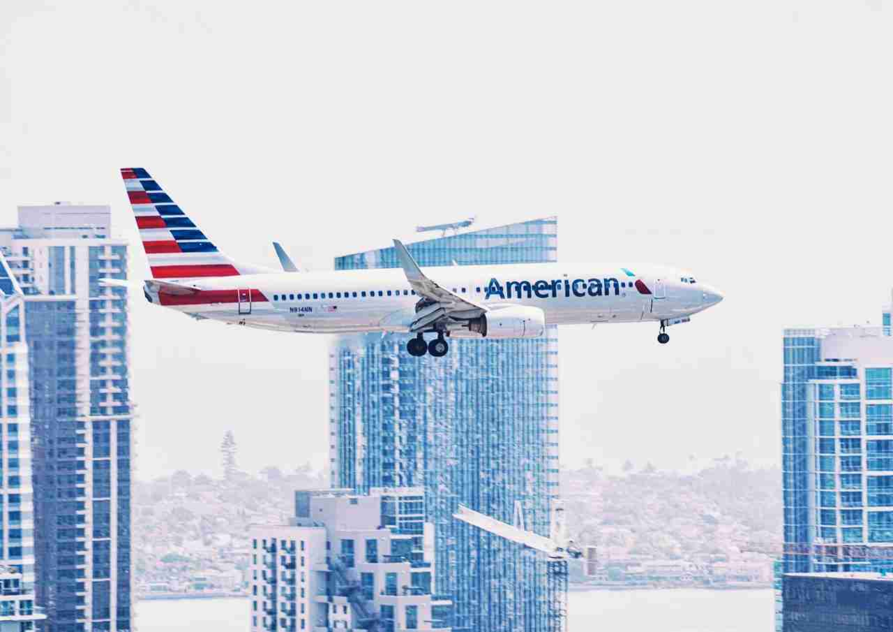 An American Airline plane coming in for a landing with the San Diego city skyline and bay in the background. (Photo by @TonyTheTigersSon via Twenty20)