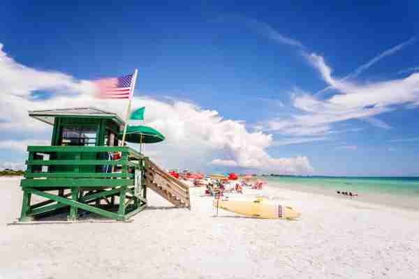 Coast Guard Beach house and beach, Siesta Key, Florida. United States flag and sufboard in a sunny day. Featured image by Pola Damonte/Getty Images