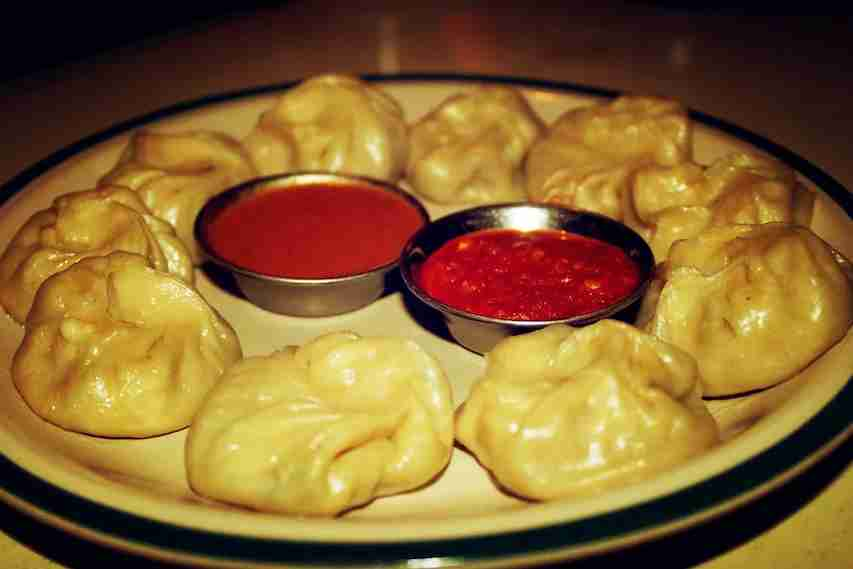 Steamed vegetarian momos with hot sauce. Image courtesy of Lora-Sutyagina via Getty Images.