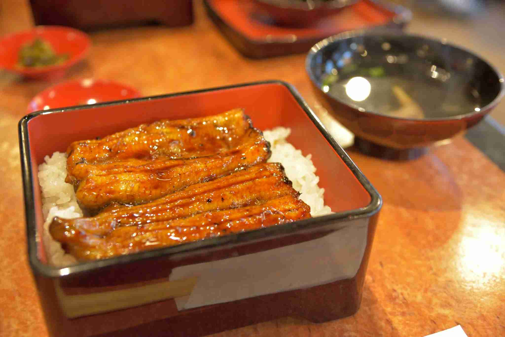<em>Unaju</em> is <em>unagi</em> on rice served in a lacquered box. Image courtesy of Kosei Saito via Getty Images.