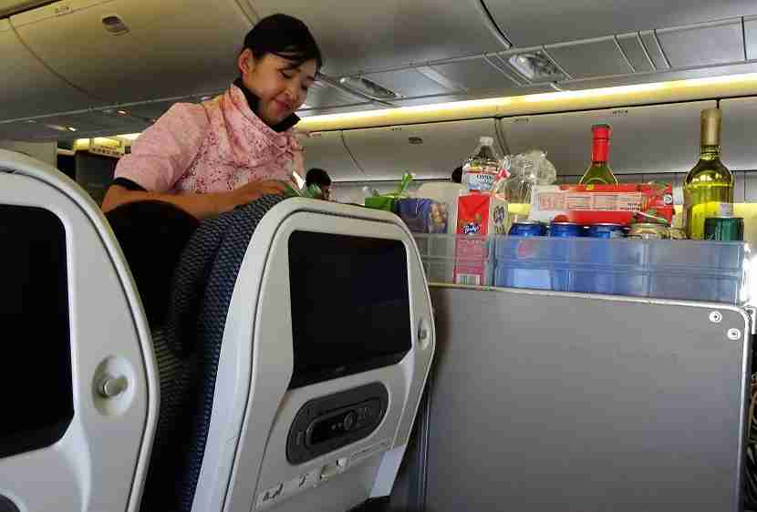 One of five flight attendants in Economy busy at work.