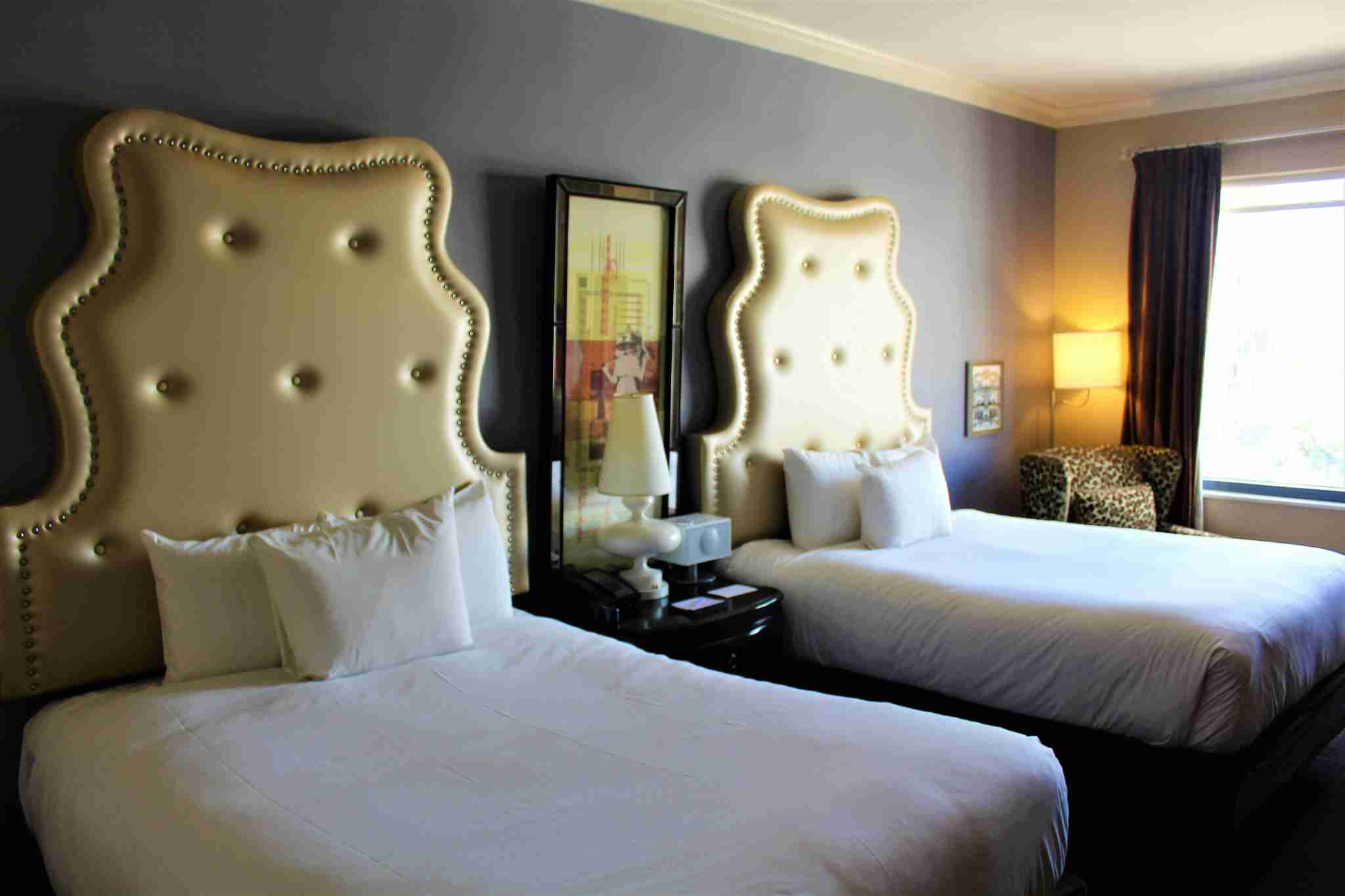 Two queen beds with chic headboards added to the room