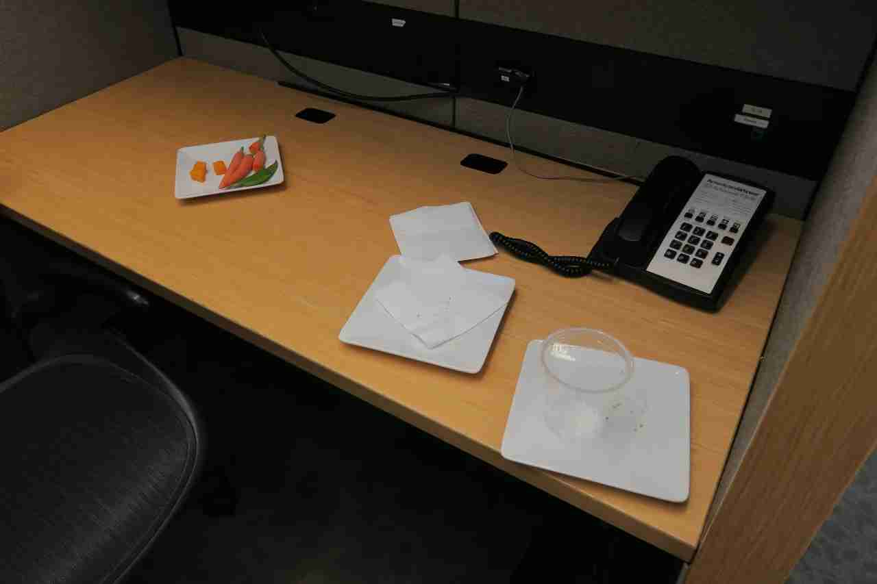 All of the unoccupied desks contained used plates or trash.
