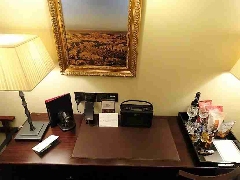 The desk with a tray of minibar offerings and a handwritten note.