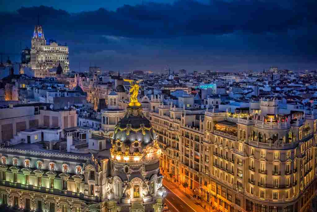 Buildings of La Gran Vía de Madrid at night with the lighting and beauty of its streets. Panoramic view of the rooftops and streets of Madrid