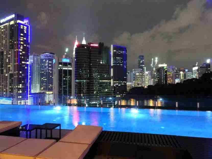 At night, the light from the pool glows beneath the tips of the Petronas Tower.