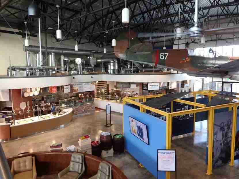A replica plane hangs over the food hall, seating and historic displays at The Proud Bird