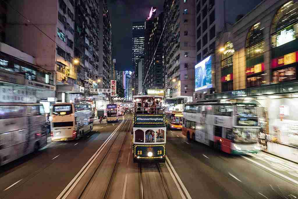 Trams and buses speed through Hong Kong. Photo courtesy of Anthony Kwan via Getty.