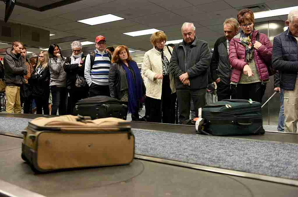 Air Canada passengers stand at the Terminal 2 baggage carousel looking for their luggage on Sunday, Jan. 8, 2017, at Fort Lauderdale-Hollywood International Airport. The Terminal 2 baggage area remained partially opened Sunday. (Taimy Alvarez/Sun Sentinel/TNS via Getty Images)