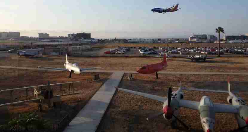 A Southwest jet prepares to land at LAX with vintage aircraft in the air park at The Proud Bird.