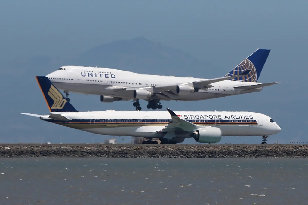 A United 747-400 lands while a Singapore Airlines A350 taxies to takeoff.
