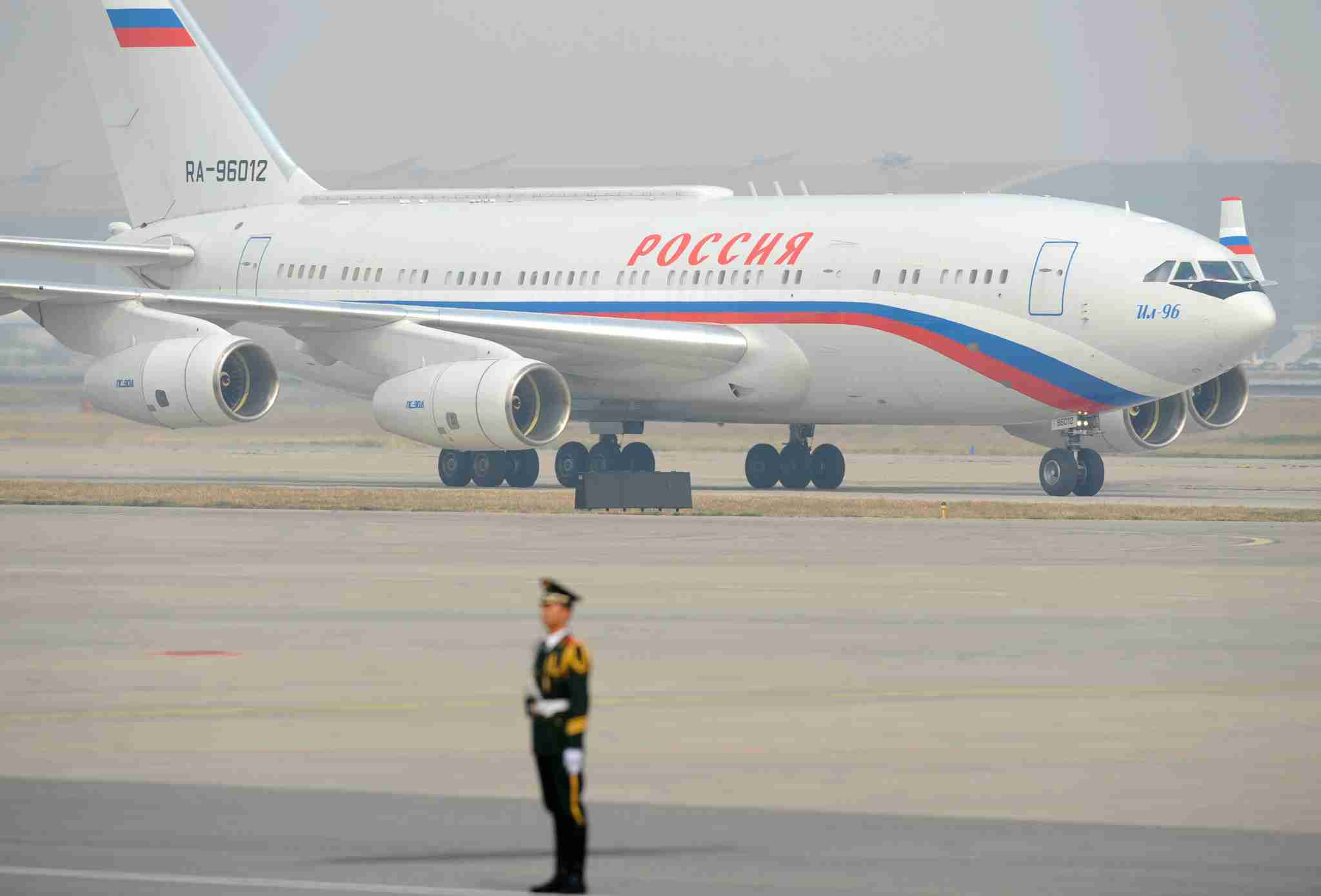 A guard stands before a plane carrying Russia