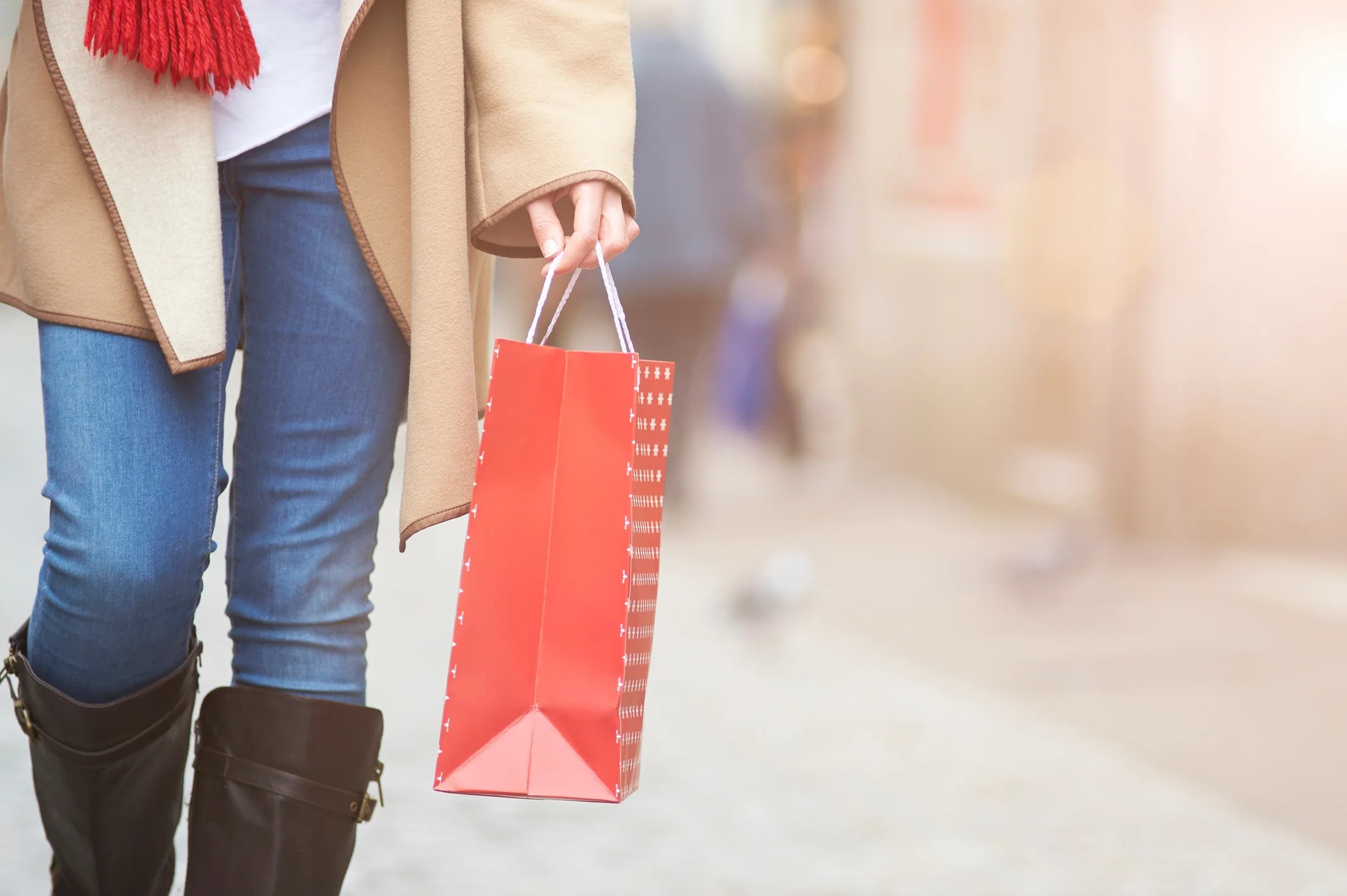 A woman carries a Christmas gift.