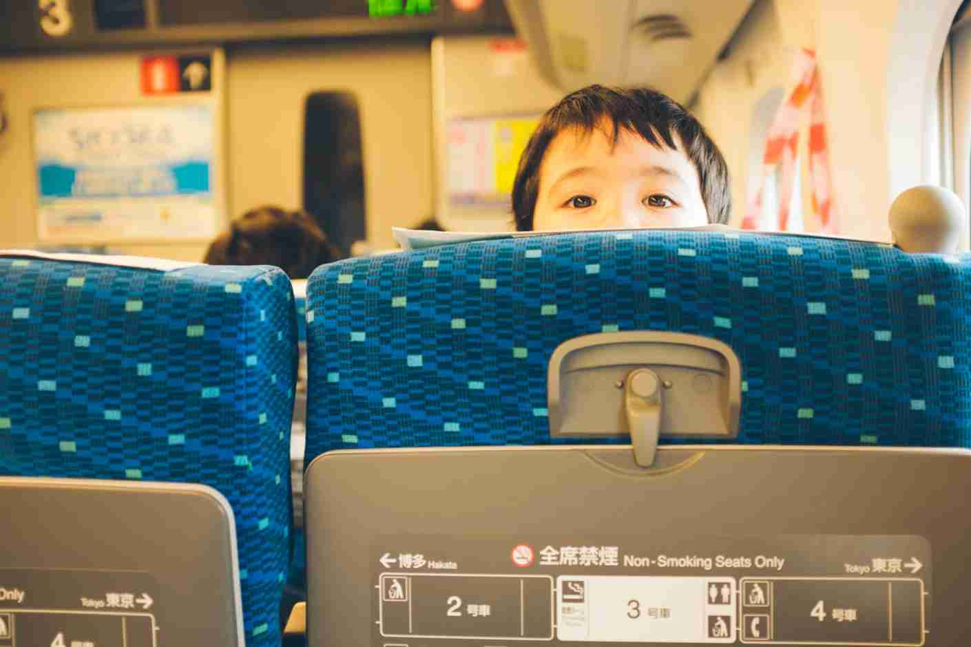 A young boy looking back over the seat of a bullet train in Japan