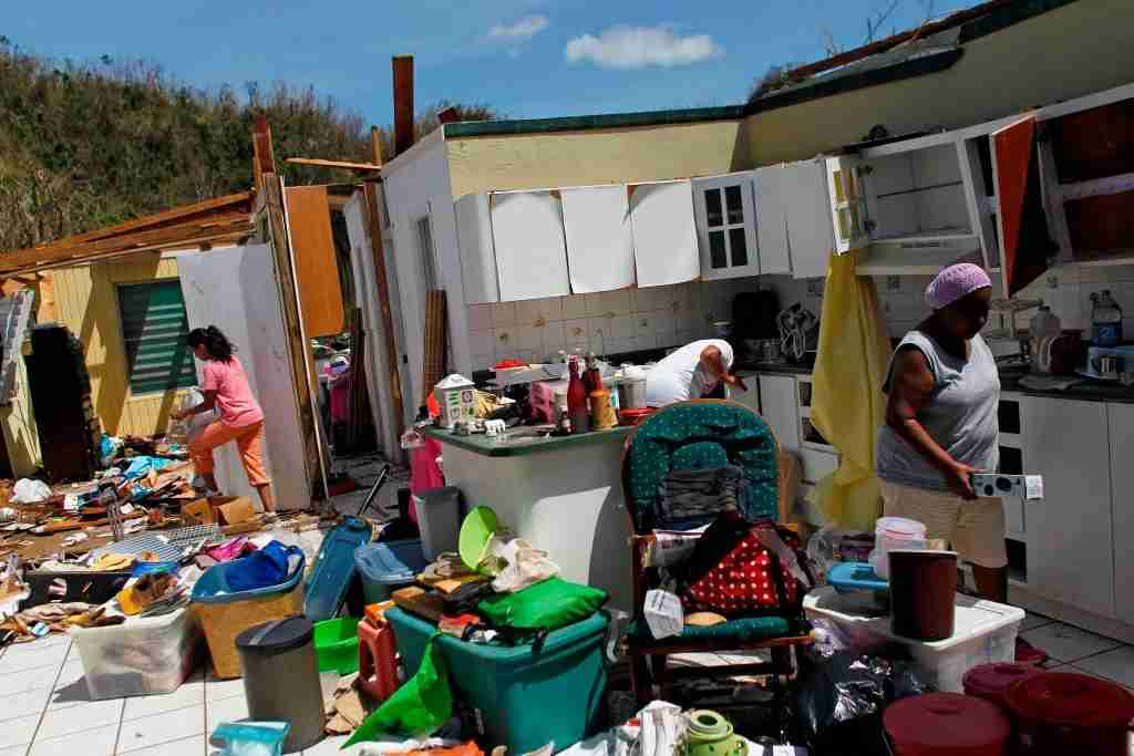 TOPSHOT - Family members collect belongings after hurricane force winds destroyed their house in Toa Baja, west of San Juan, Puerto Rico, on September 24, 2017 following the passage of Hurricane Maria.Authorities in Puerto Rico rushed on September 23, 2017 to evacuate people living downriver from a dam said to be in danger of collapsing because of flooding from Hurricane Maria. / AFP PHOTO / Ricardo ARDUENGO (Photo credit should read RICARDO ARDUENGO/AFP/Getty Images)