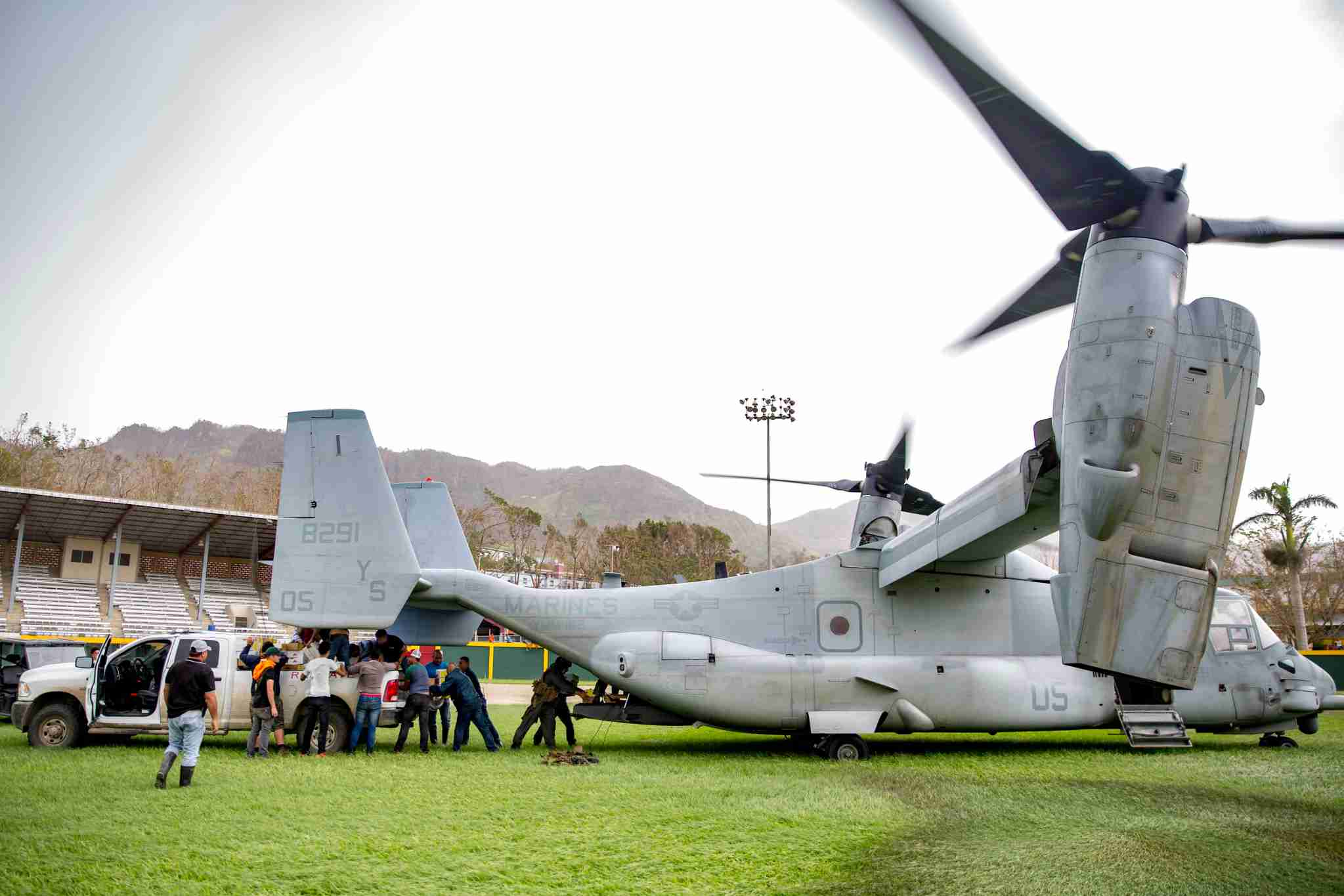 Marines from the amphibious assault ship USS Kearsarge and area residents unload food and drinking water from an MV-22 Osprey aircraft September 27, 2017 in Jayuya, Puerto Rico.(Photo by Ryre Arciaga/US Navy via Getty Images)
