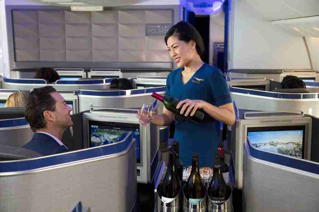 A United Airlines flight attendant serves wines in Polaris international business class. Image courtesy of United Airlines.
