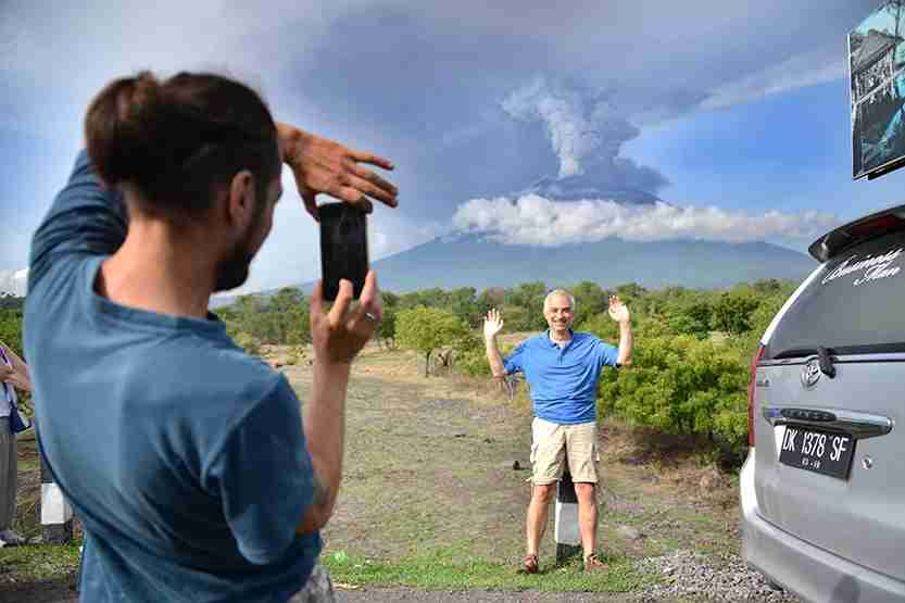 A foreign tourist takes pictures in front of Mount Agung erupting seen from Kubu sub-district in Karangasem Regency, on Indonesia