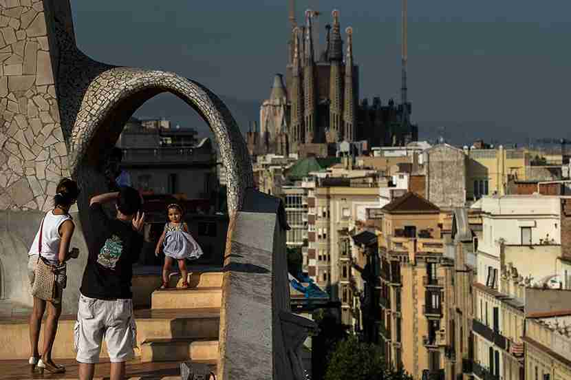 BARCELONA, SPAIN - JULY 24: A couple take pictures of their daughter at the roof of the building