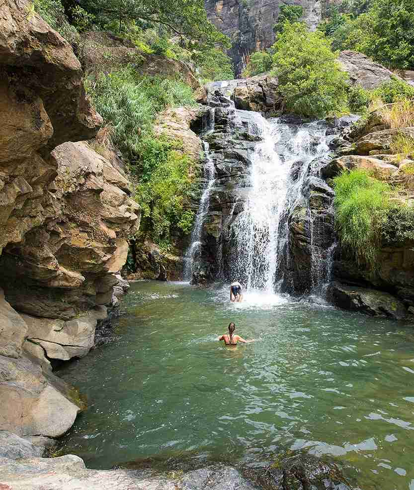 Tourists enjoy a swim at the Rawana Waterfall near Ella, Sri Lanka. Photo by Nick Brundle Photography / Getty Images.