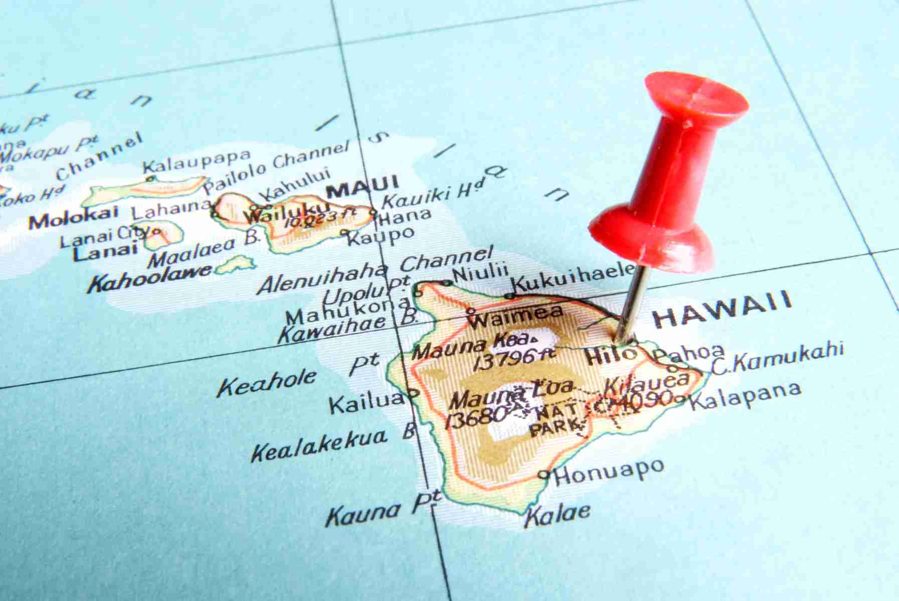 Red pin stuck into map of Hawaii