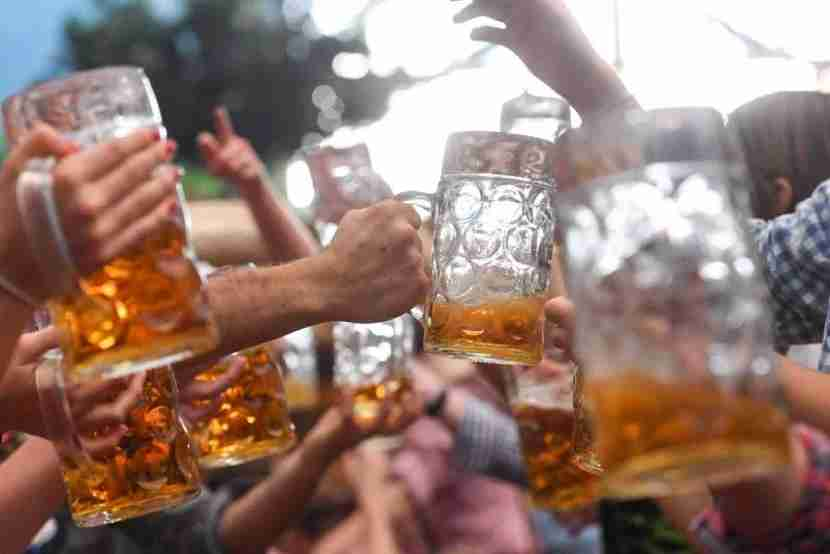 Visitors of the Oktoberfest beer festival clink their beer glasses on September 24, 2017 at the Theresienwiese fair grounds in Munich, southern Germany.The World
