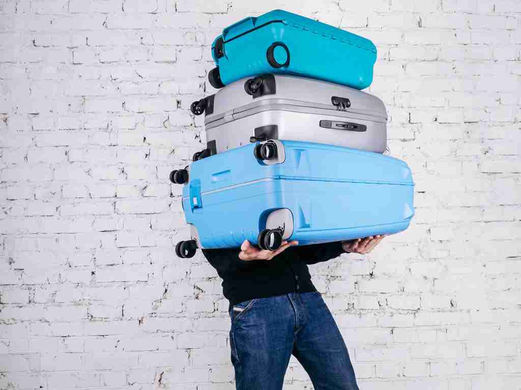 Man holding three heavy suitcases in hand. Travel light. Man holding three heavy suitcases in hand. Travel light. (Photo by ULU_BIRD/Getty Images)