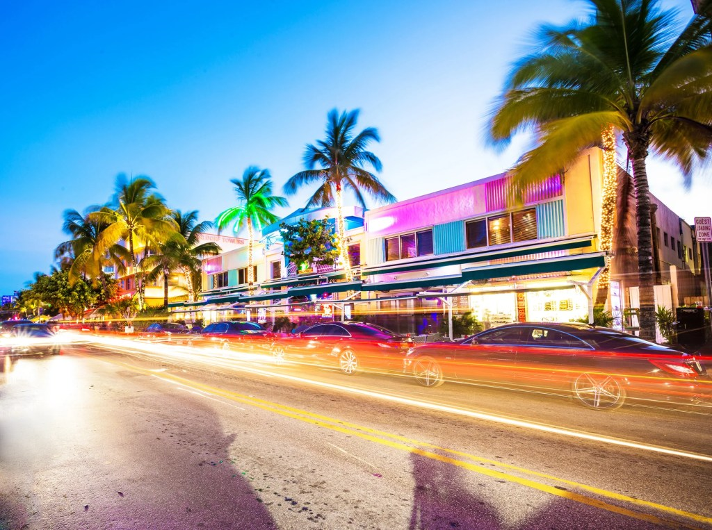 Ocean Drive scene at night with neon lights, palm trees, cars and people having fun, Miami beach. Art Deco style hotels and restaurants at sunset on Ocean Drive, world famous destination for it
