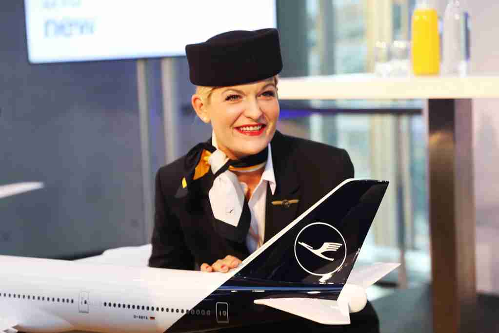 A Lufthansa flight attendant poses with a model of the carrier