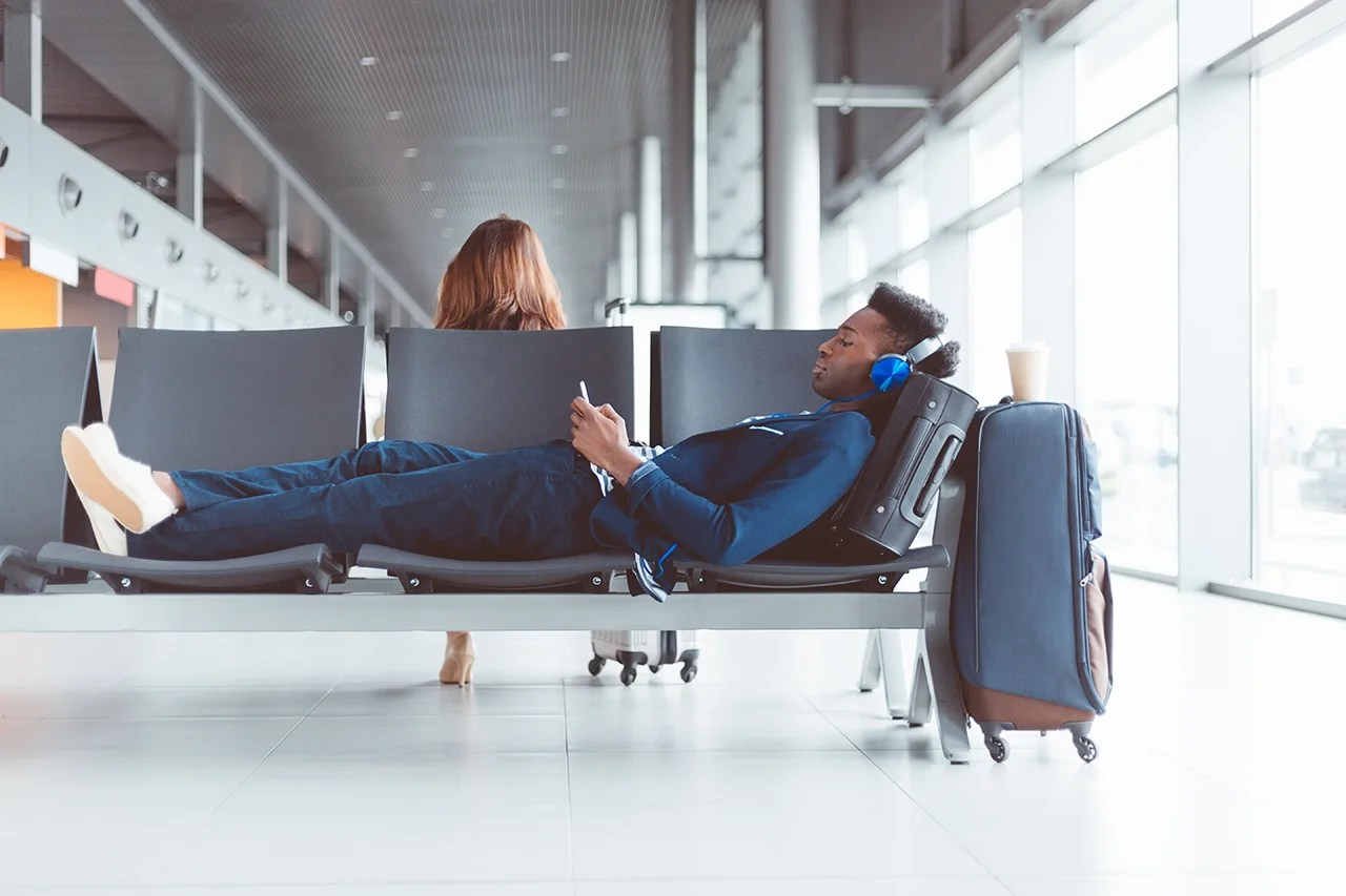 Shot of young african man lying on chairs at lounge with his luggage and listening music on mobile phone, waiting for flight. (Photo by izusek/Getty Images)