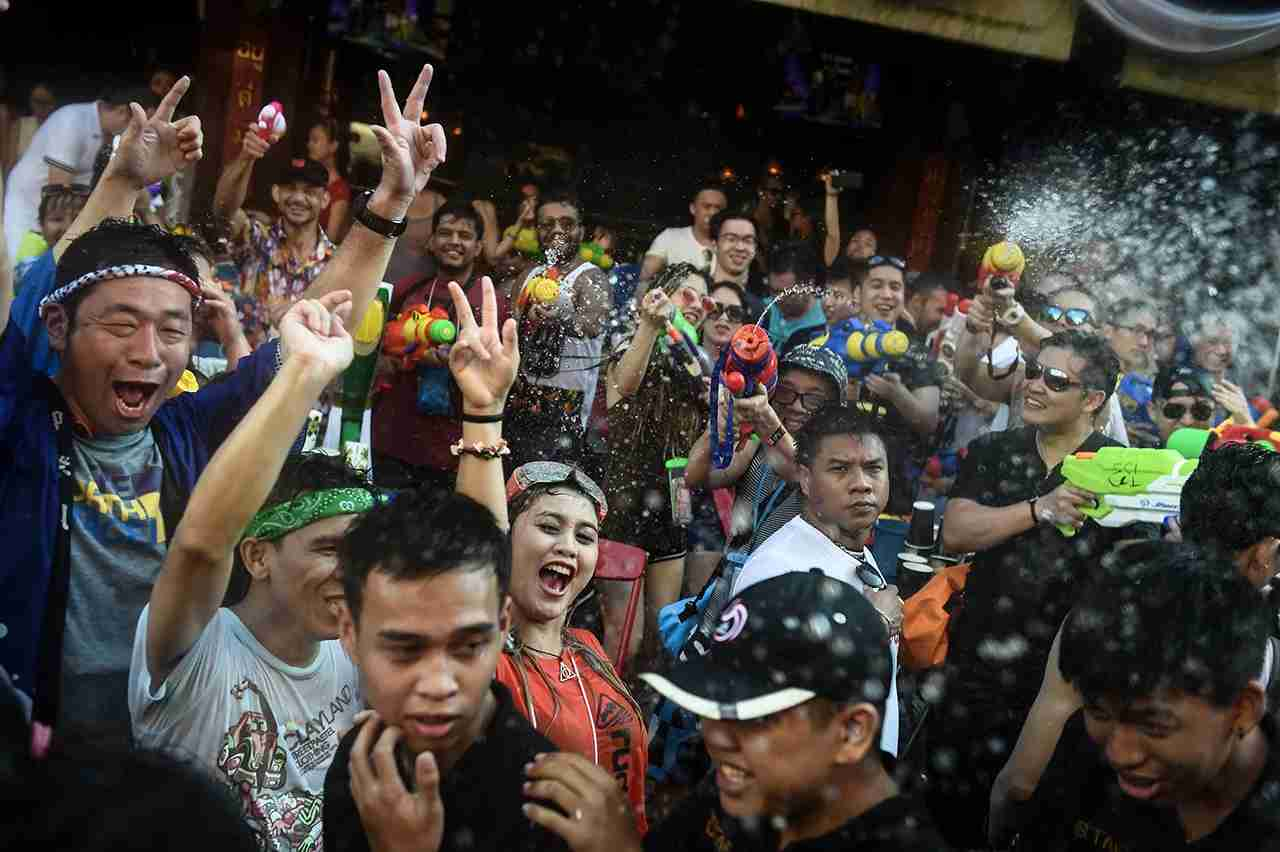 People gather in front of a bar during Songkran, or the Thai New Year, celebrations on Khaosan Road in Bangkok. (Photo by LILLIAN SUWANRUMPHA/AFP/Getty Images)