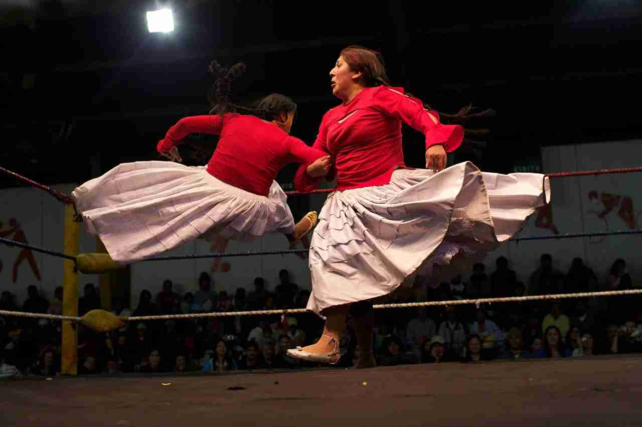 Cholita wrestler Martha La Altena (right) fights with a male wrestler dressed as a Cholita during the