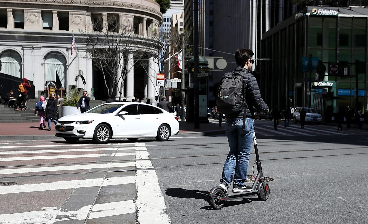 A user rides a Bird scooter on April 17, 2018 in San Francisco, California. (Photo by Justin Sullivan/Getty Images)
