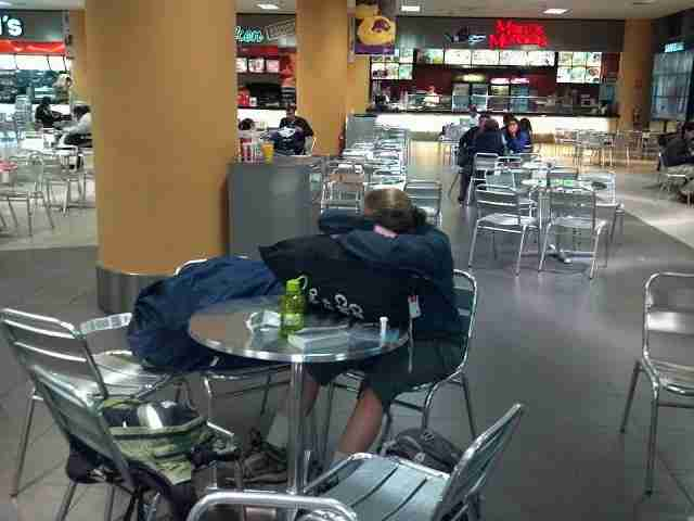 TPG contributor (and my wife) Katie Genter sleeping in the Lima Airport food court.