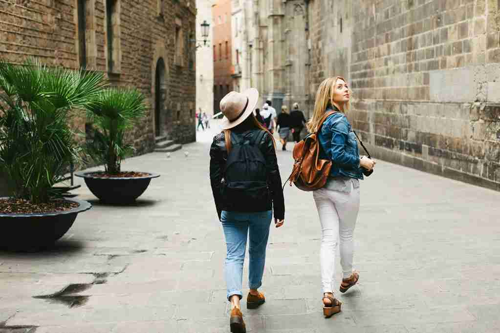 Spain, Barcelona, two young women walking in the city. (Photo by Westend61/Getty Images)