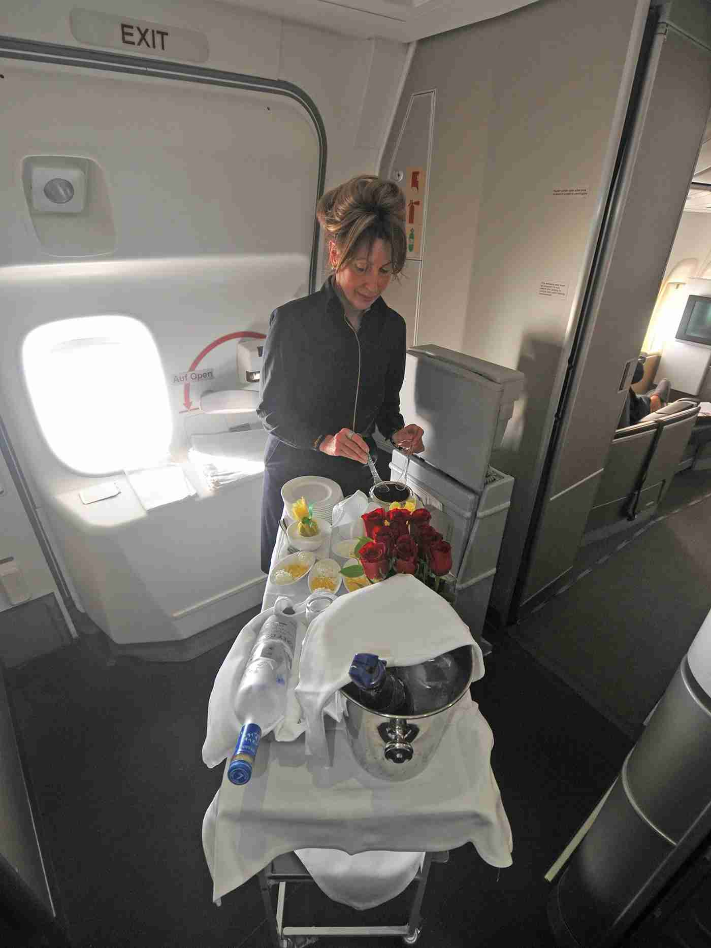 A flight attendant prepares a caviar appetizer in the first-class galley of a Lufthansa 747-8 in flight from Miami to Frankfurt (Photo by Alberto Riva / The Points Guy)