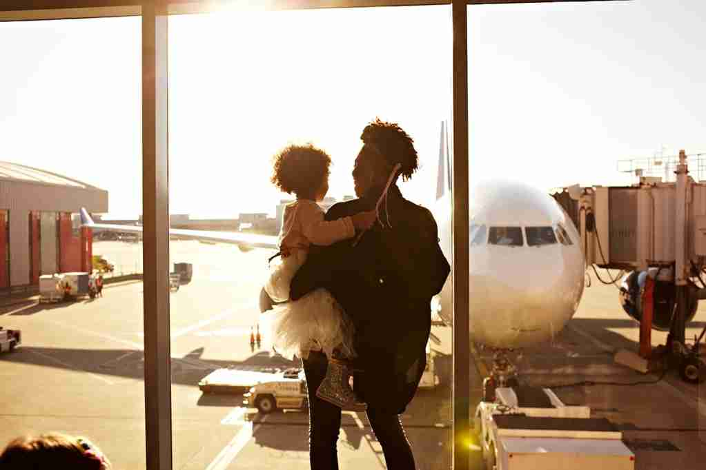 Mother holding daughter at airport (Photo by Granger Wootz/Getty Images)