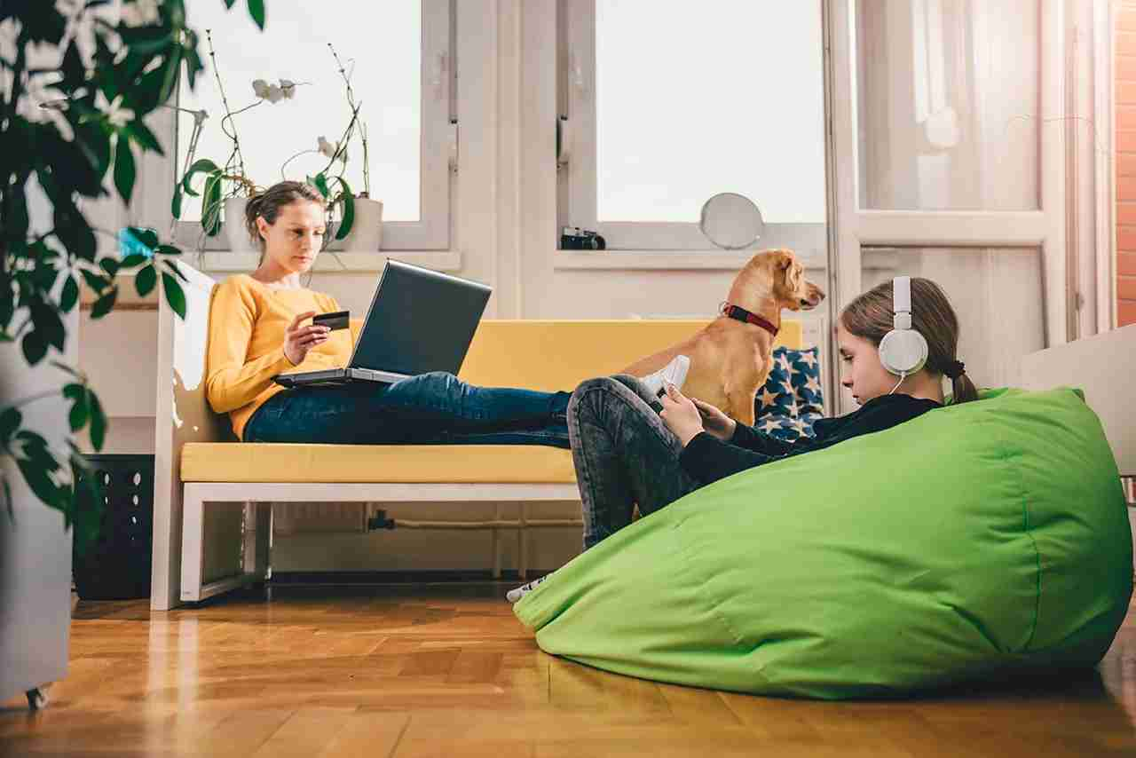 Woman wearing yellow sweater sitting on yellow sofa at home and shopping online with credit card. (Photo by Kerkez / Getty Images)