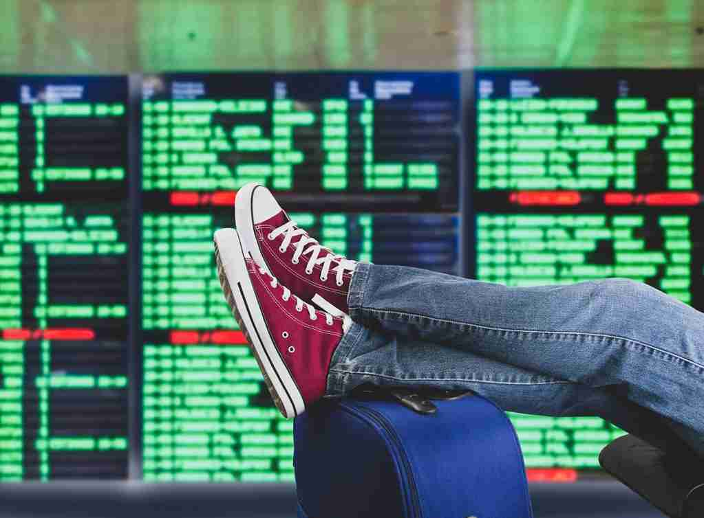 young man waiting for the plane at international airport with the flight information board. (Photo by Manuel-F-O/Getty Images)