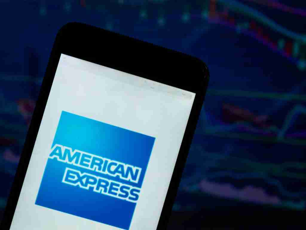KIEV, UKRAINE - 2018/08/04: The American Express logo seen displayed on a smart phone with a background of a stock market shedle. The American Express Company, also known as Amex, is an American multinational financial services corporation headquartered in Three World Financial Center in New York City. (Photo by Igor Golovniov/SOPA Images/LightRocket via Getty Images)