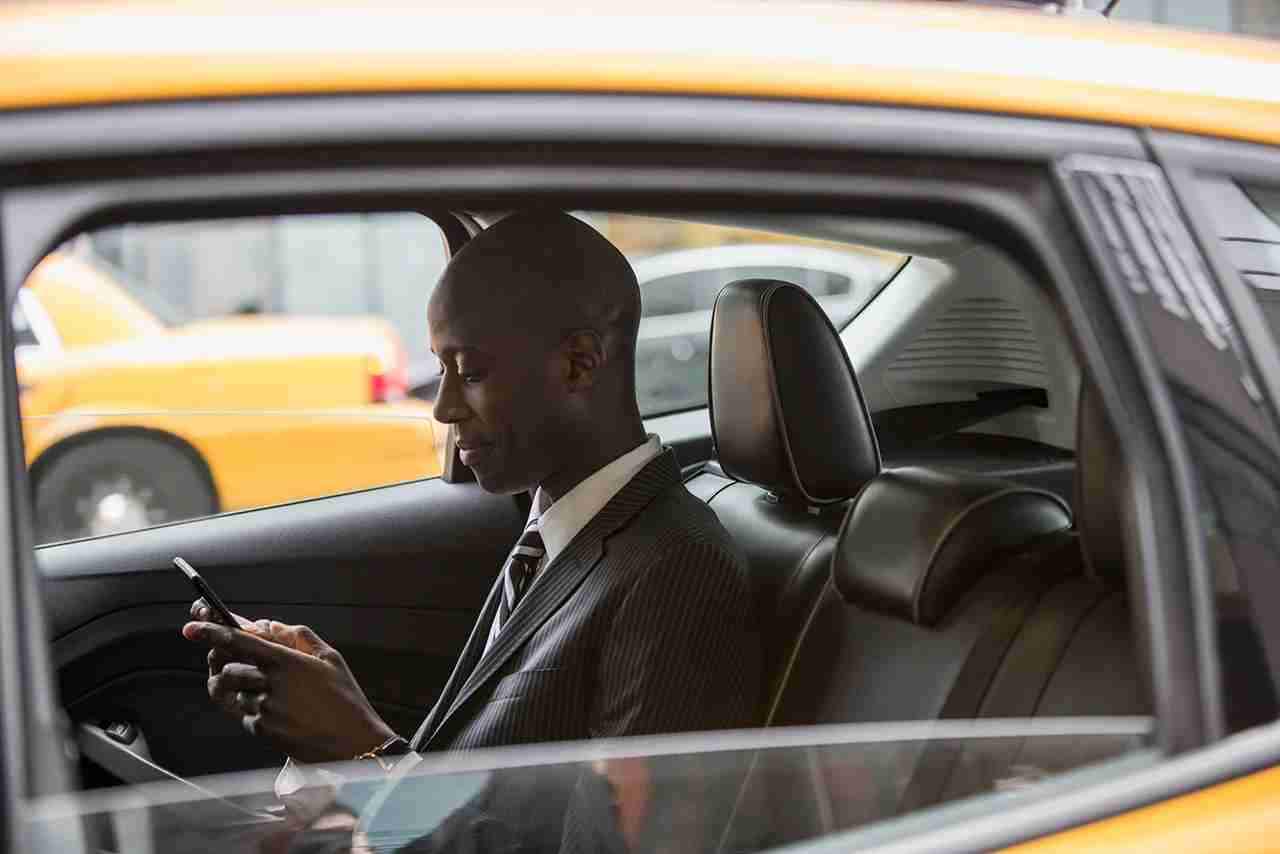 Black businessman riding in taxi on city street. (Photo by Jose Luis Pelaez Inc/Getty Images)
