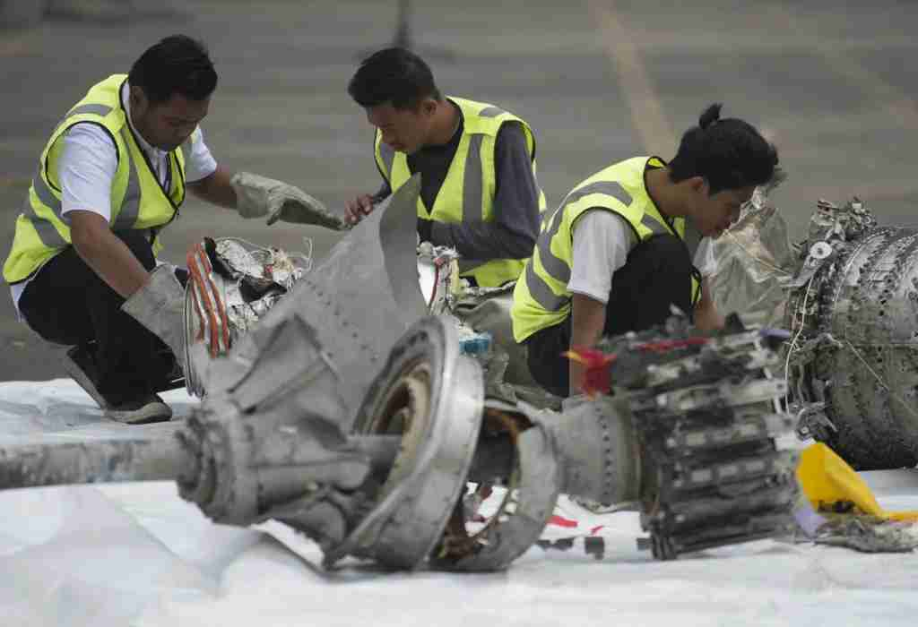 Investigators examine engine parts from the ill-fated Lion Air flight JT 610 at a port in Jakarta on November 7, 2018, after they were recovered from the bottom of the Java sea. - The Indonesian Lion Air jet that plunged into the Java Sea on October 29, killing all 189 on board, had an air speed indicator problem on its fatal flight and on three previous journeys, the country