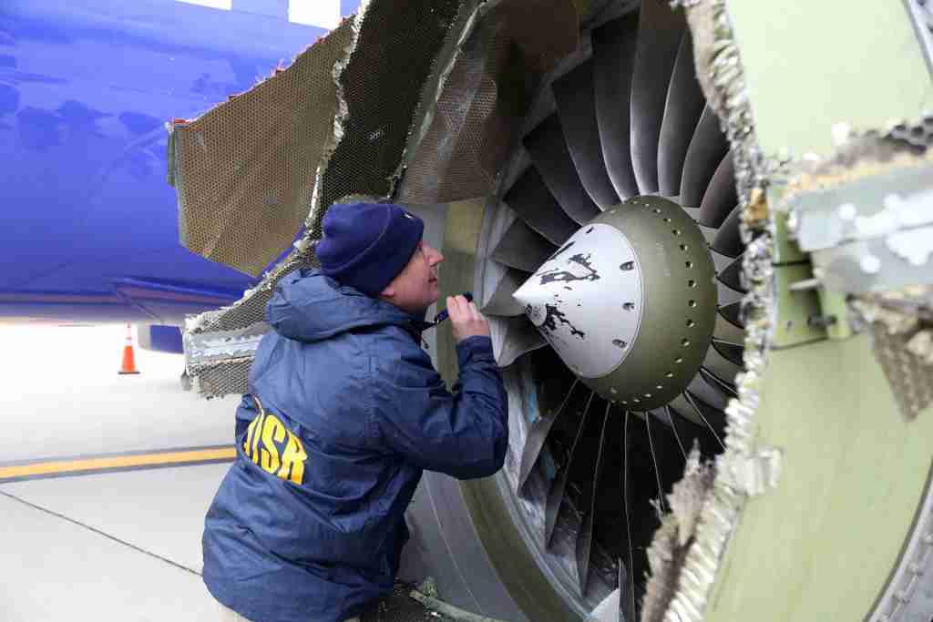 PHILADELPHIA, PA - APRIL 17: In this National Transportation Safety Board handout, NTSB investigator Jean-pierre Scarfo examines damage to the CFM International 56-7B turbofan engine belonging Southwest Airlines Flight 1380 that separated during flight Philadelphia International Airport April 17, 2018 in Philadelphia, Pennsylvania. Investigators can
