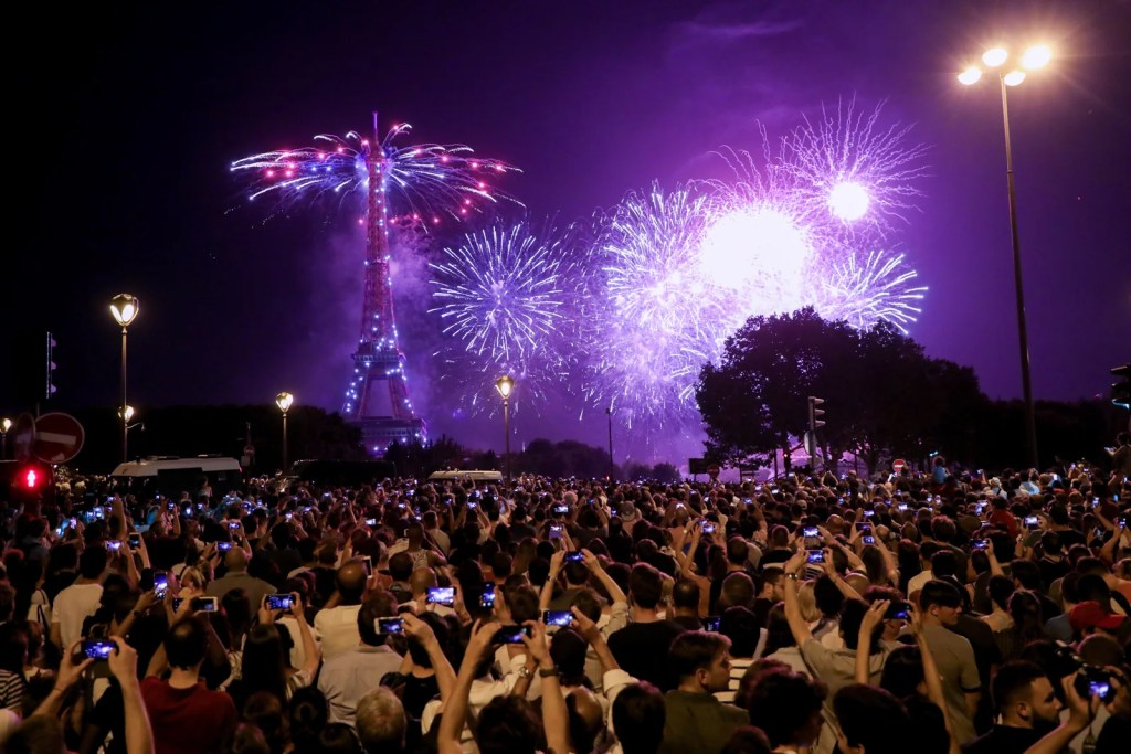 People enjoy the traditional Bastille day fireworks over the Eiffel Tower from the Pont de l